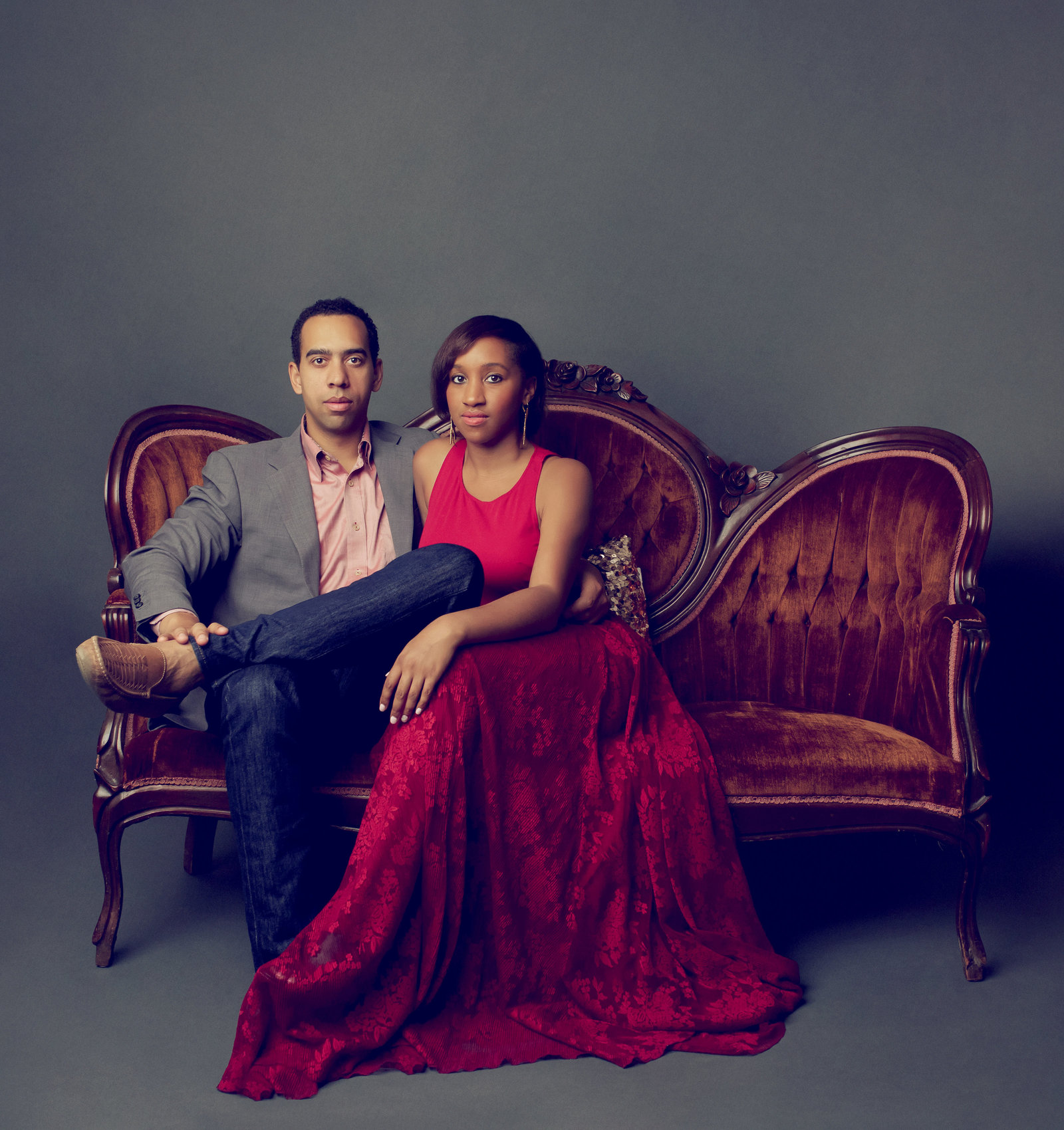 High end portrait of man in jeans and a blazer and woman in a red dress, sitting on an antique sofa. Family portraits Houston.
