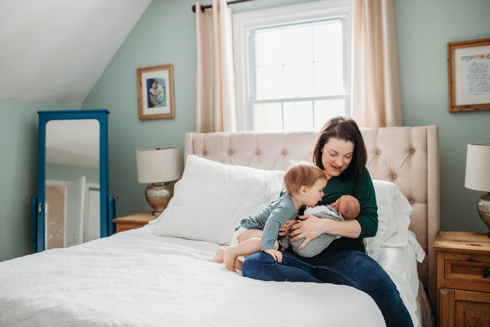 mother in mint green room holds baby boy with toddler on bed in bolton ma