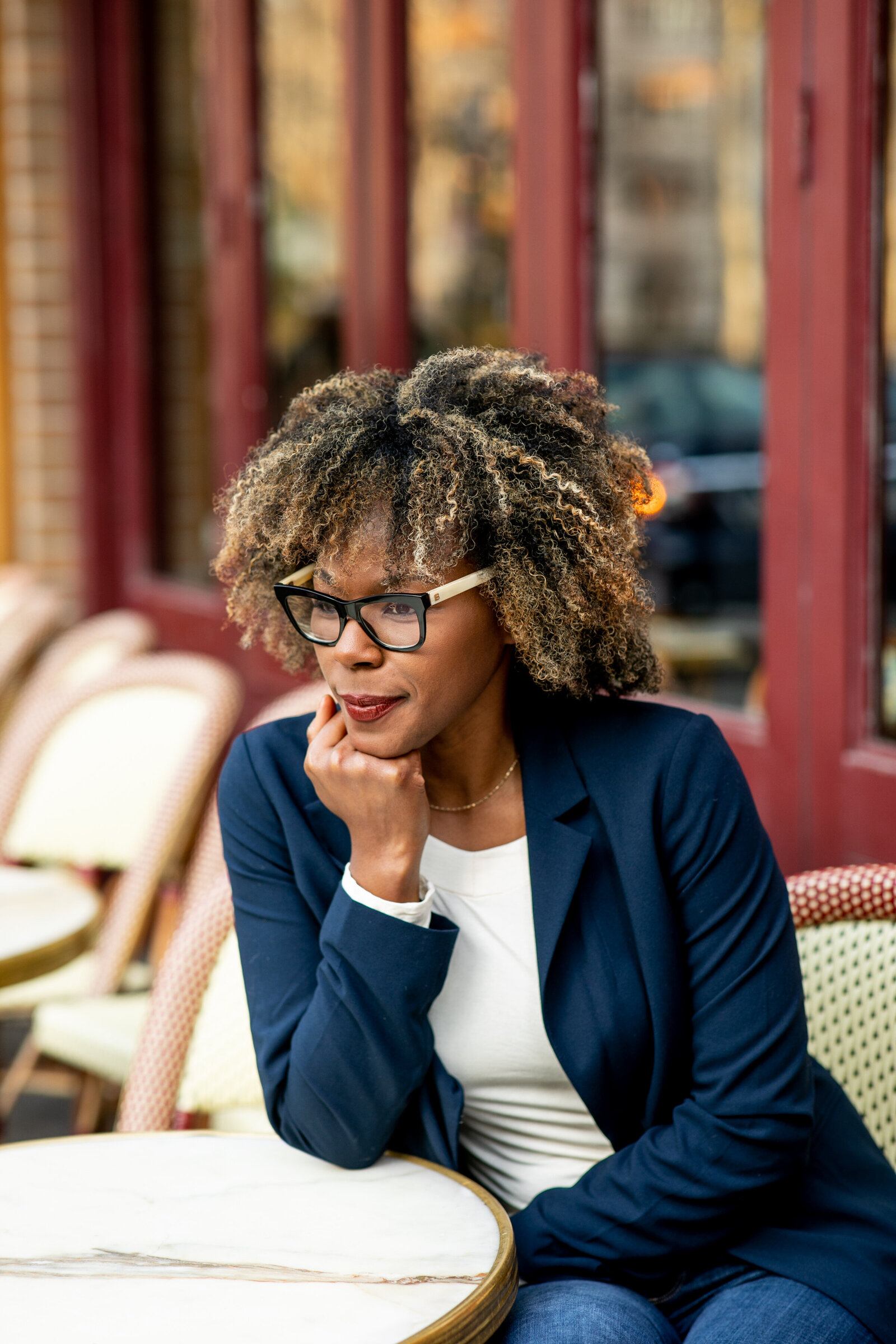 black woman with glasses at city restaurant