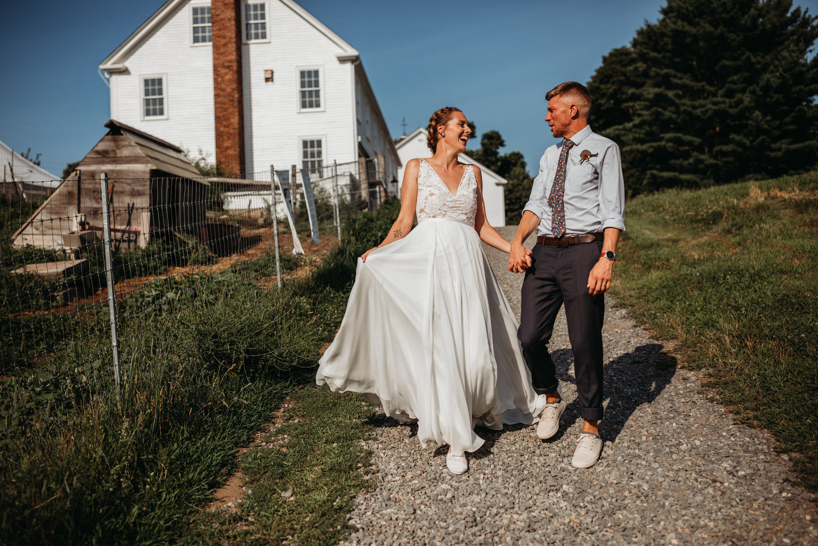 bride and groom walk hand in hand at farm wedding in massachusetts