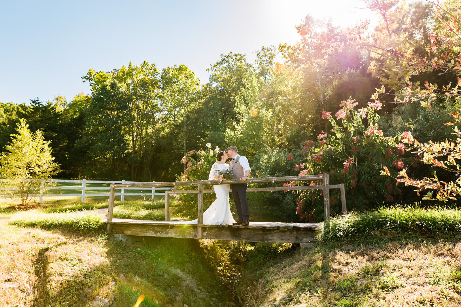 Bright, sunny landscape with bride and groom kissing at Chaumette Winery