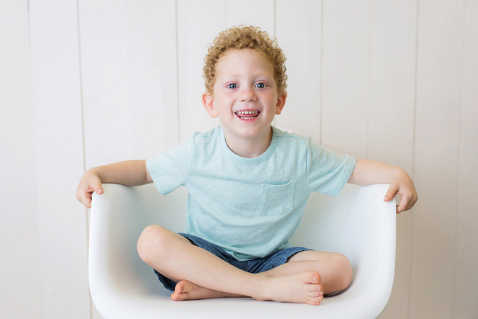 young boy in blue shirt sitting in a chair