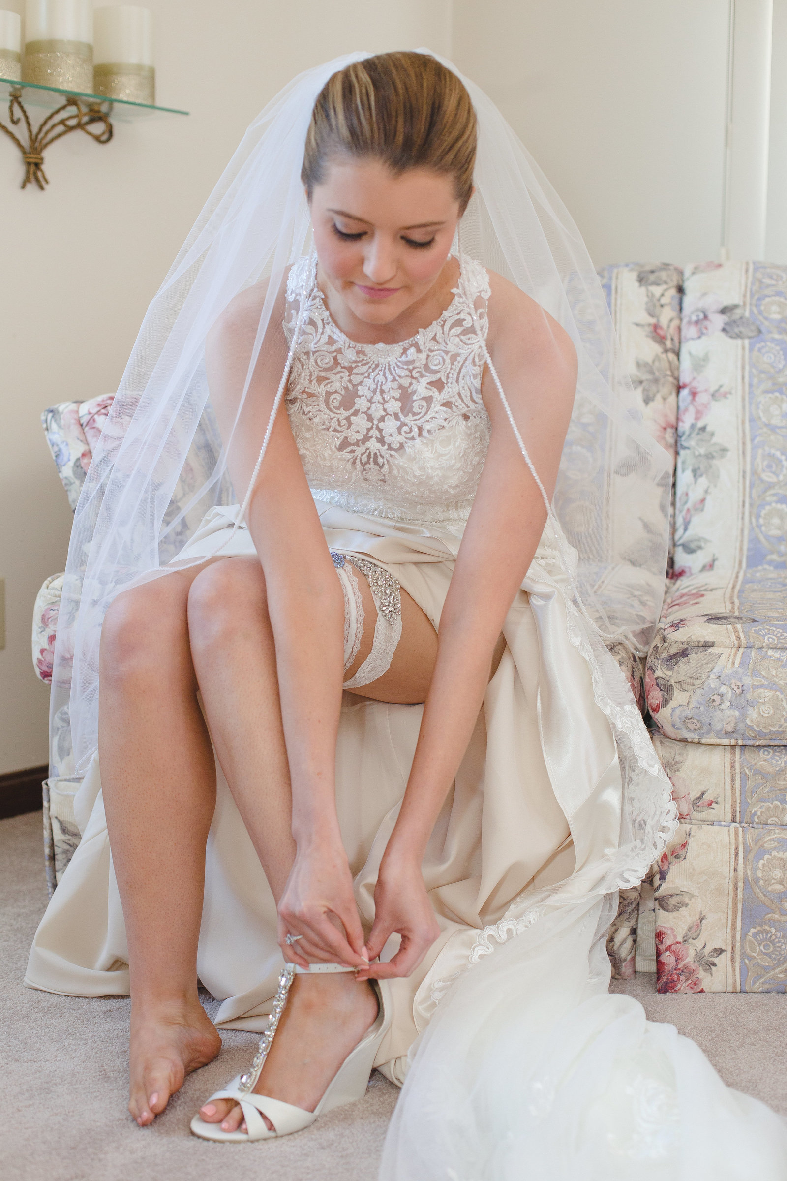 bride sits down to buckle her sparkly white wedge shoes