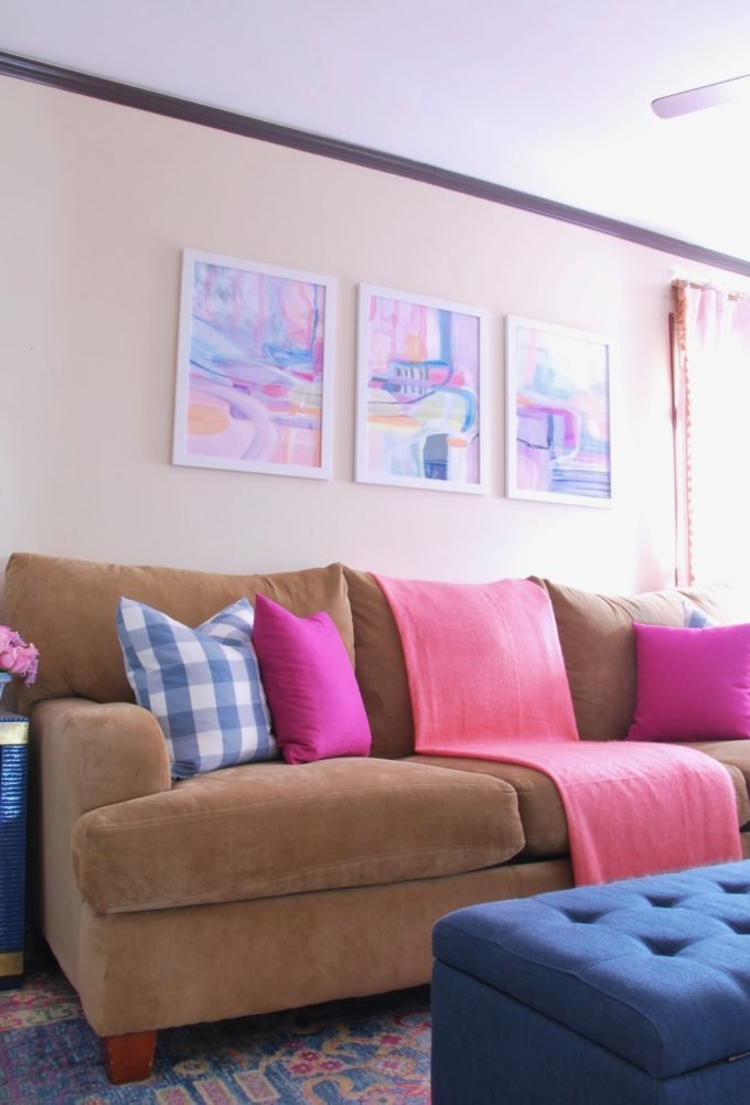 A tan sofa with color throw pillows and three framed art pieces.