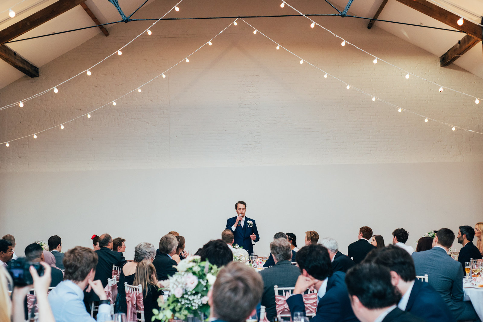 Groom giving his speech under fairy lights at relaxed Oxnead Hall wedding in Norfolk