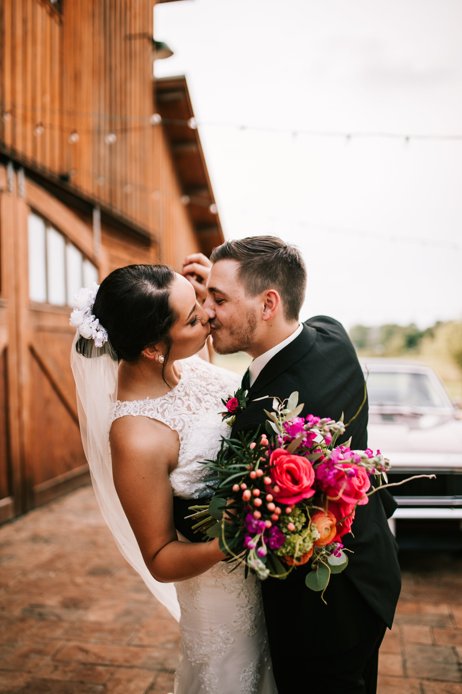 wedding with flowers, barn, and antique car in the back, kissing and holding hands