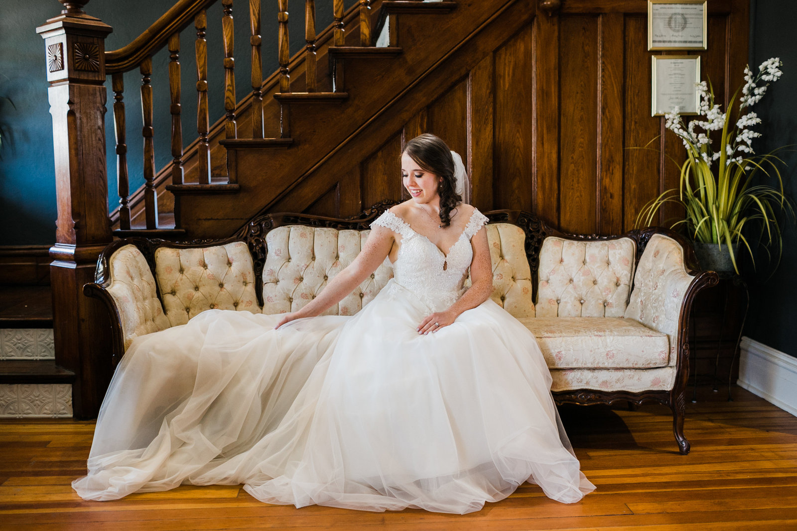 Bride, Joey, poses on a vintage couch after putting on her wedding dress. Her train drapes across the couch onto the ground.