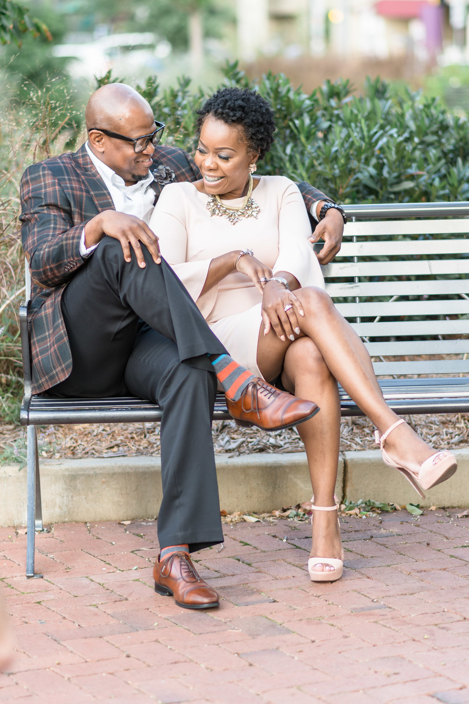 Charlotte engagement photographer shot of couple on bench in Romare Bearden Park in uptown charlotte