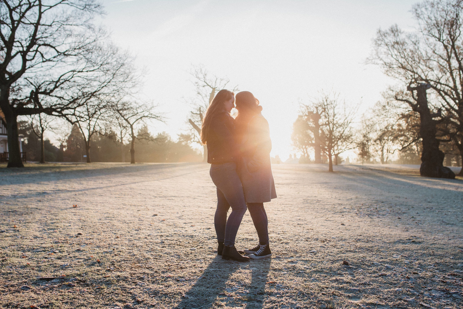 Silhouette photo of lesbian couple cuddlng in the frosty morning sun in Christchurch Park in Ipswich