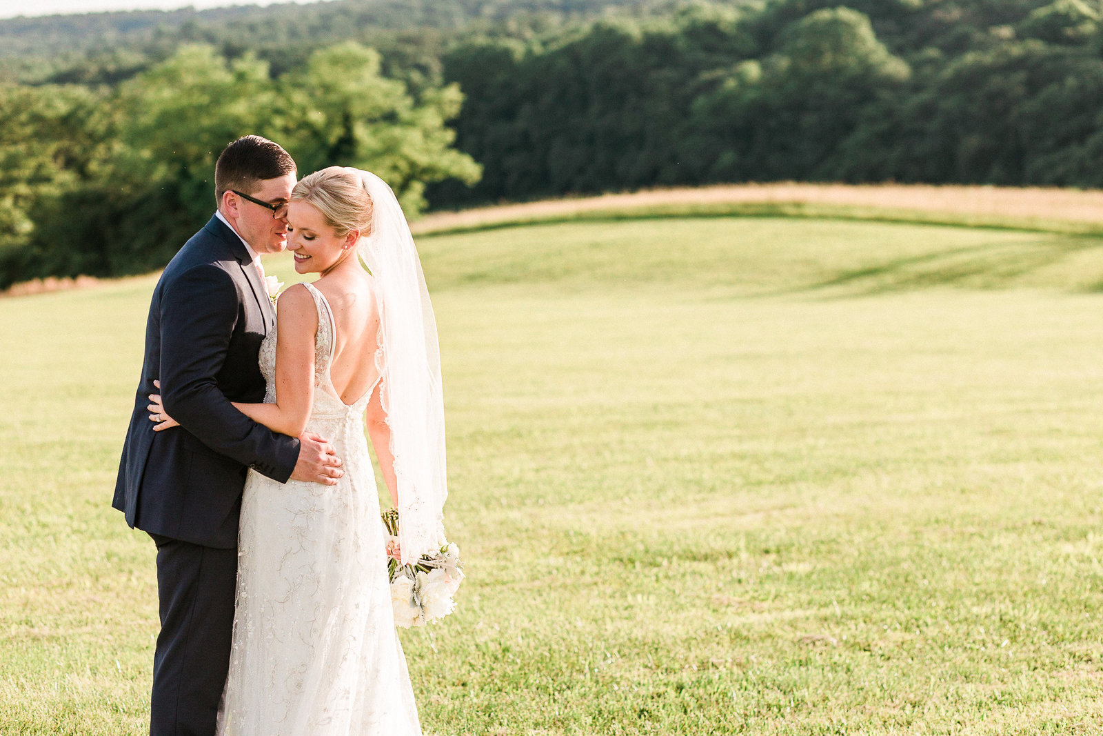 Bride in beaded gown and groom stand in a field at  Springfield Manor