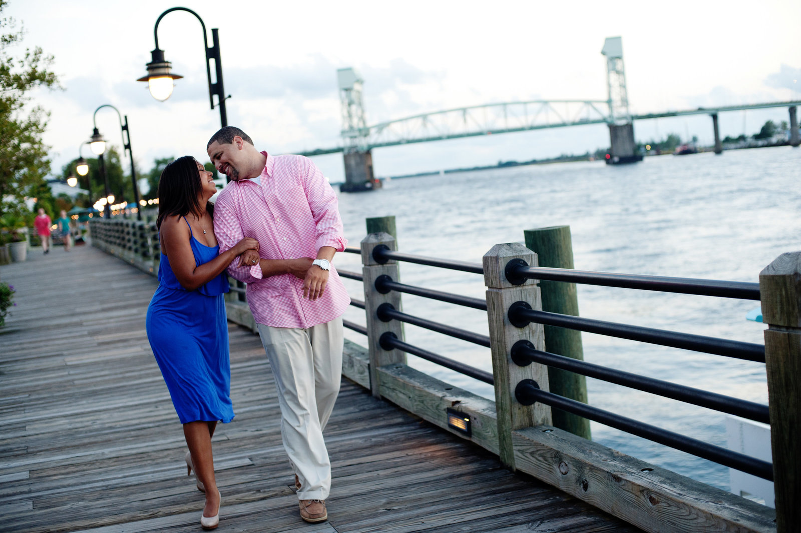a couple walk holding hands along the river in downtown wilmington