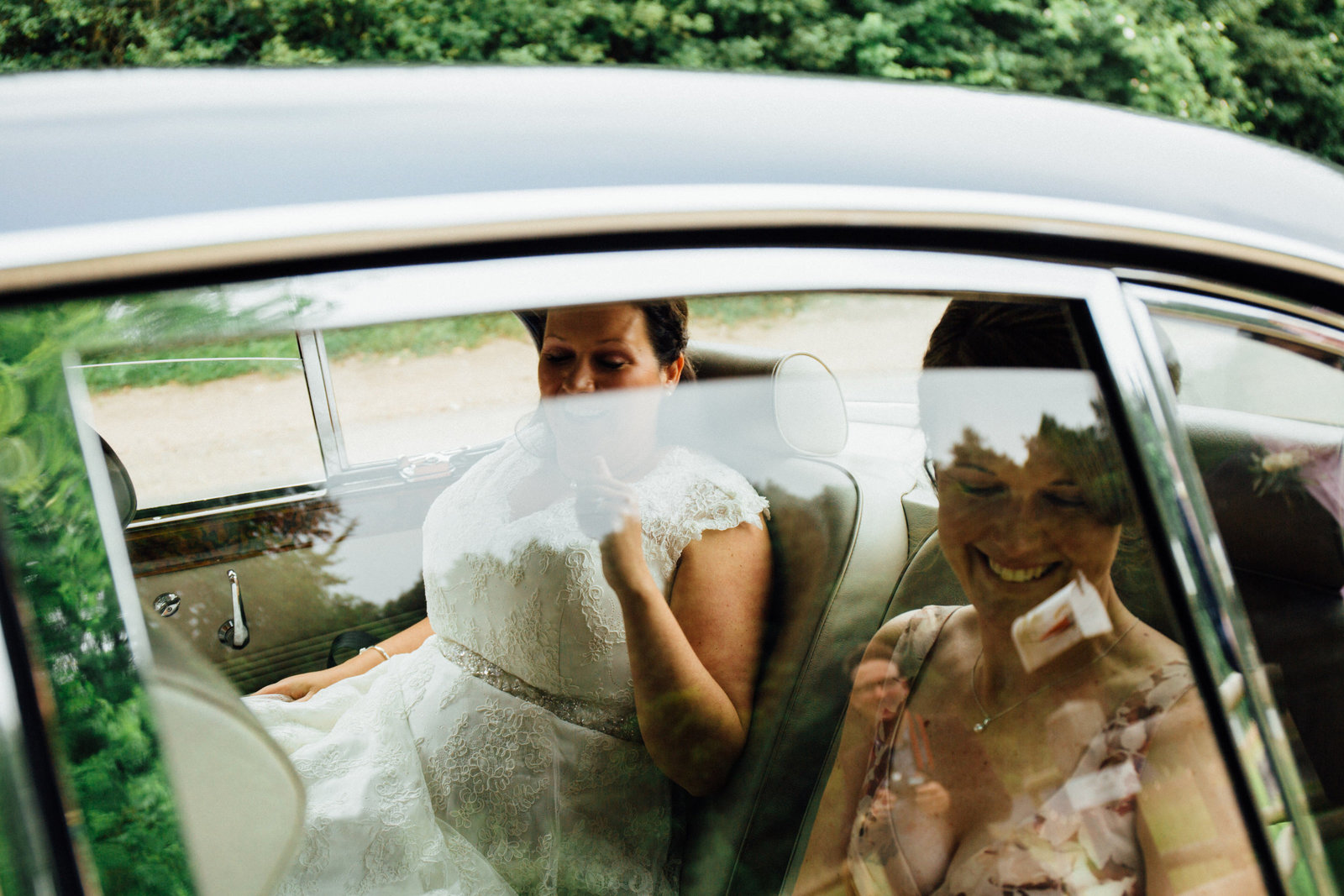 Grinning bride and bridesmaid arriving at Norwich wedding through the vintage car window