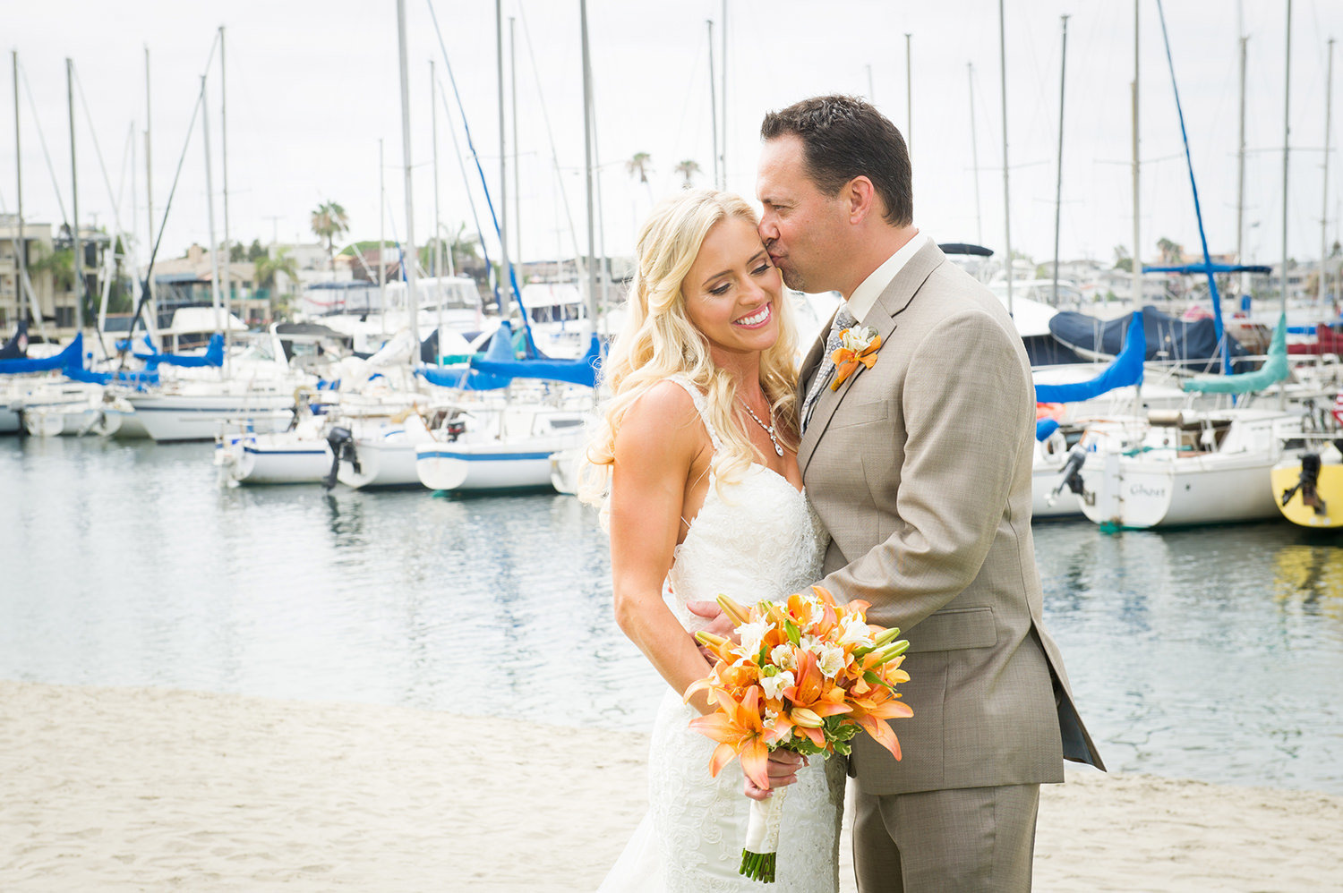groom kissing brides head with boats in the background