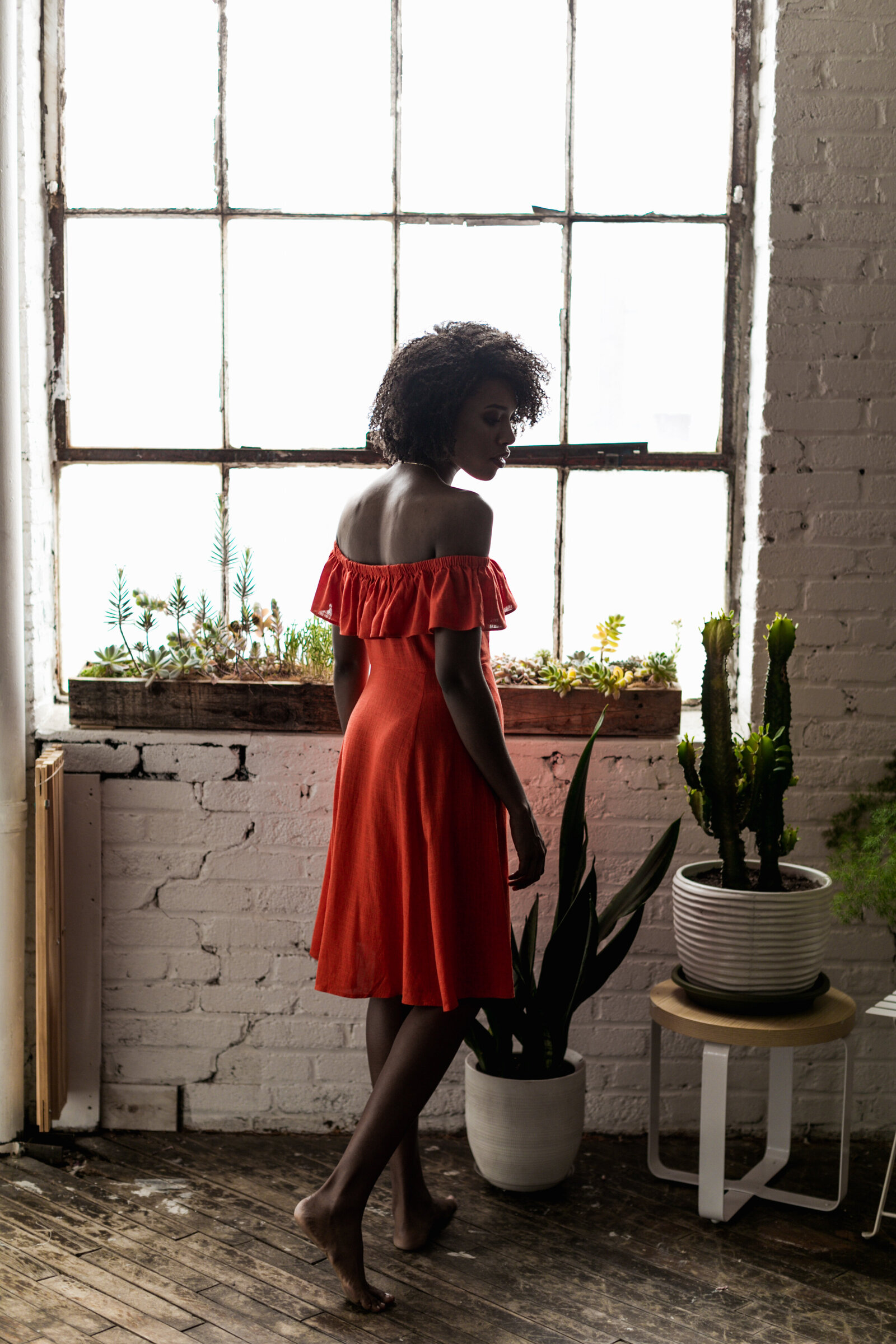woman in red dress with plants and window