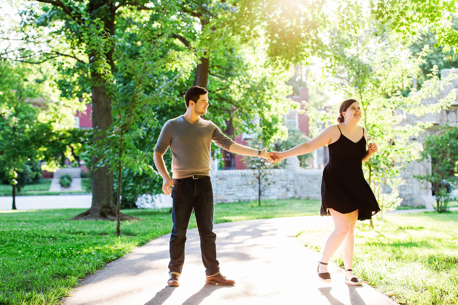 Happy engaged couple dancing together in Tower Grove Park in St. Louis