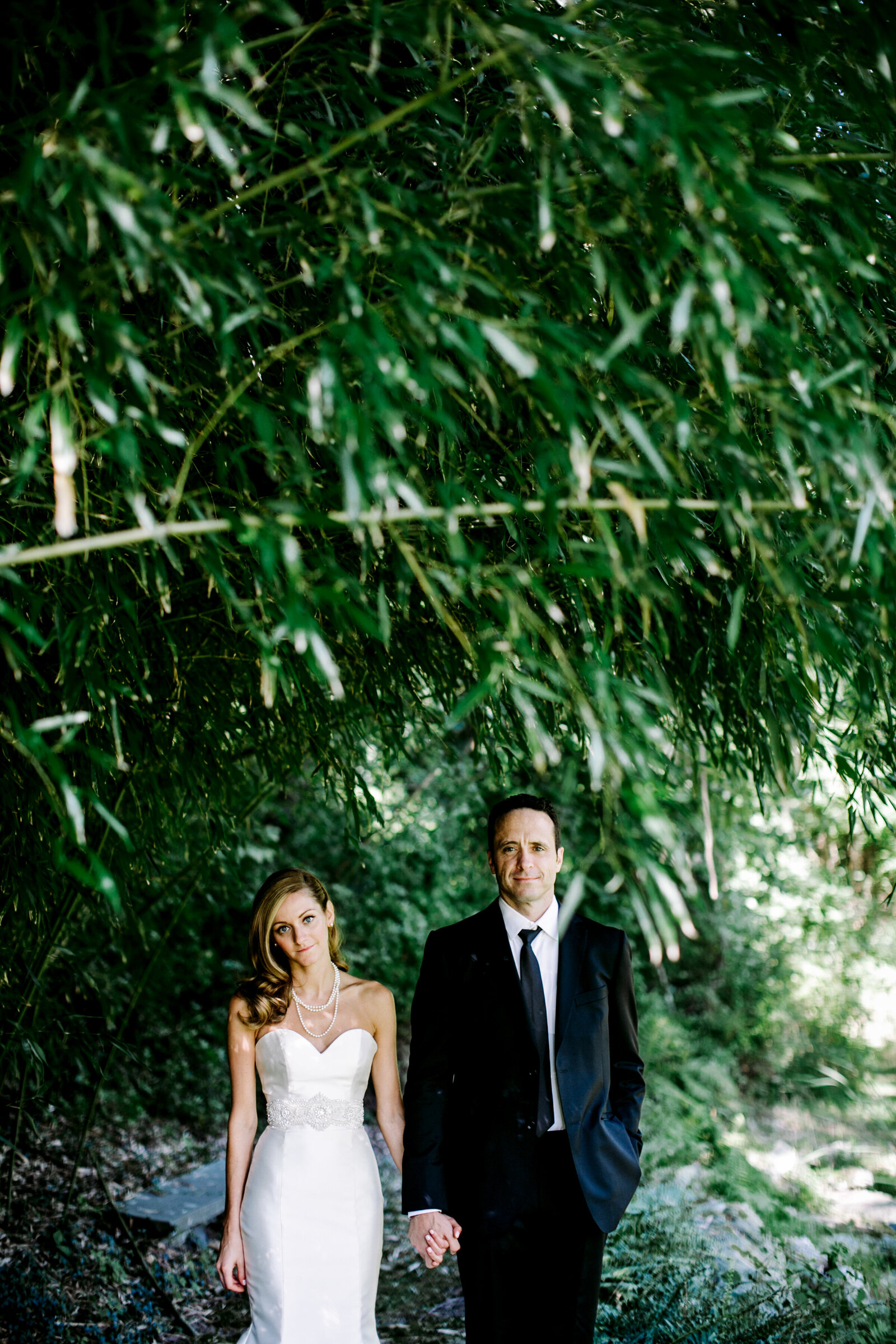 bride and groom under bamboo trees