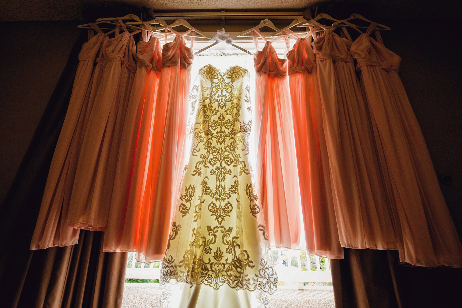 backlit image of brides and bridesmaids dress hanging in front of a window