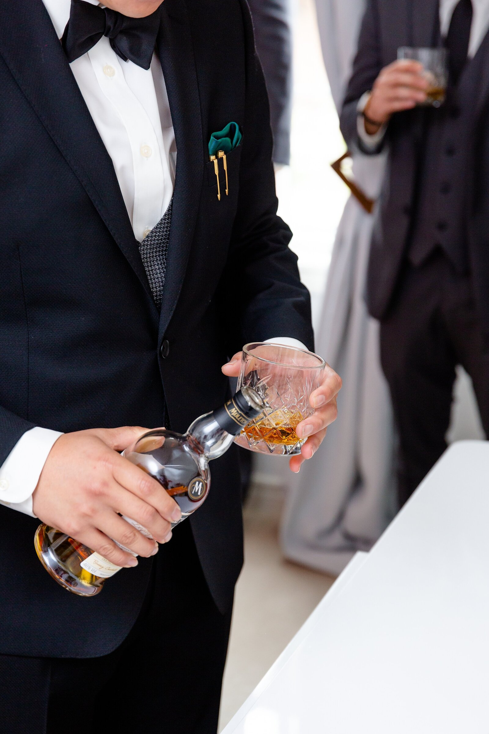 Groom-pours-glasses-of-whiskey-for-him-and-his-groomsmen