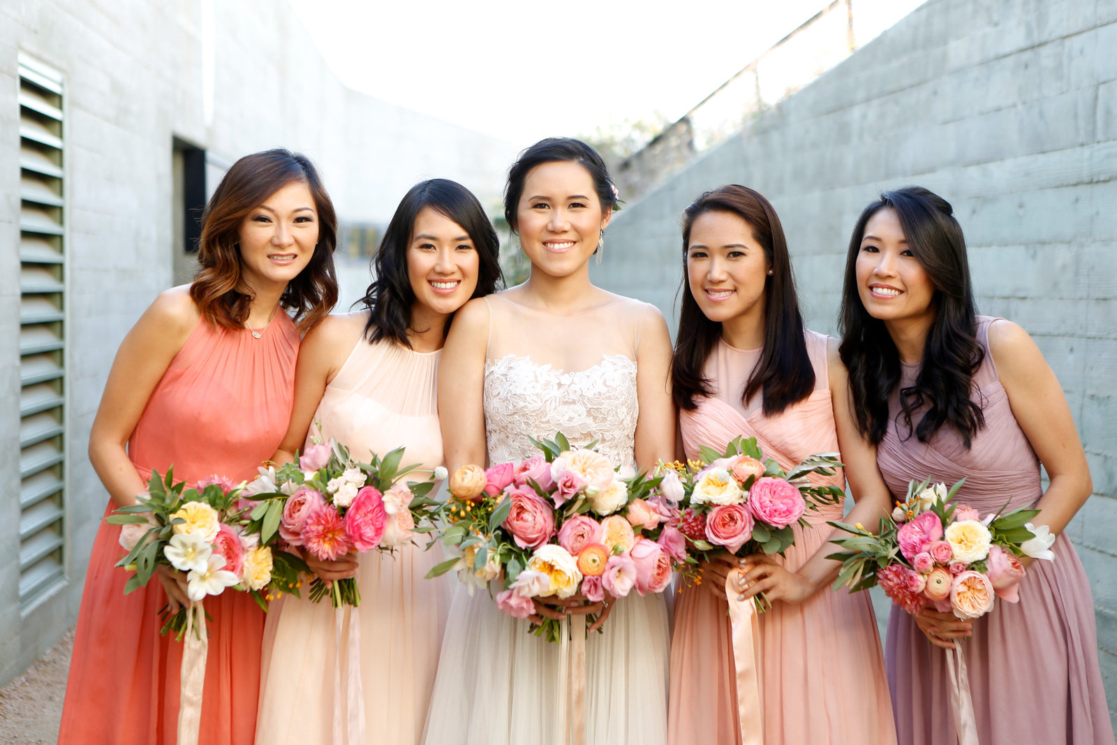 purple coral and peach bridesmaids dresses with colorful bouquets