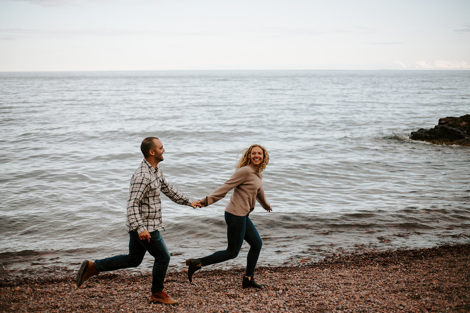 Couple holding hands running along the North Shore of Minnesota during their engagement session