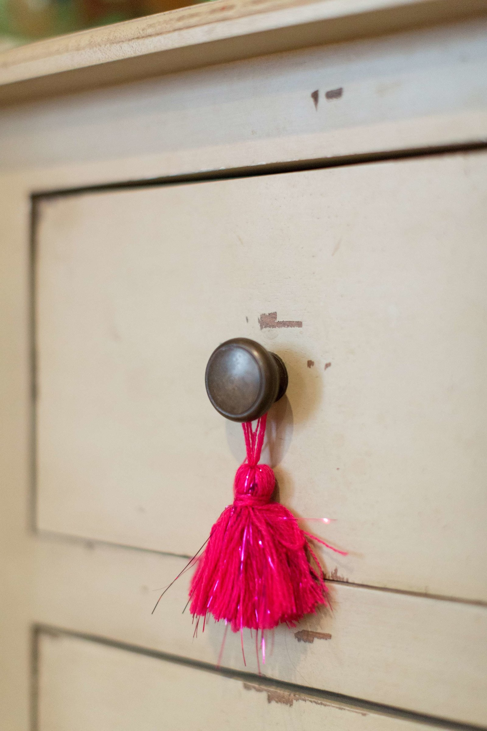 A drawer pull with hanging hot pink tassels.