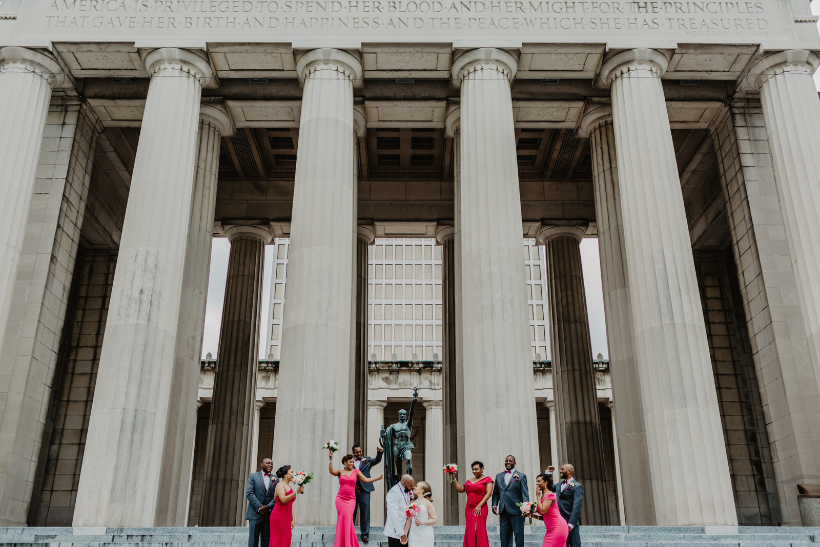 Full Bridal Party on steps on War Memorial with Bride and Groom kissing