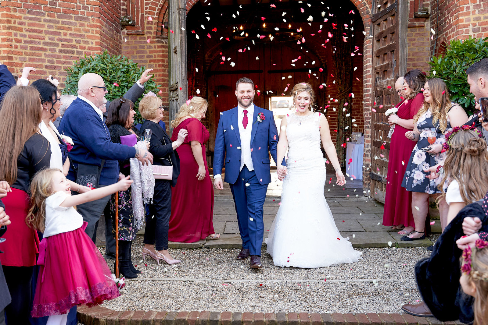 Bride and groom walking through a confetti shower at leez priory wedding venue - Essex wedding photographer