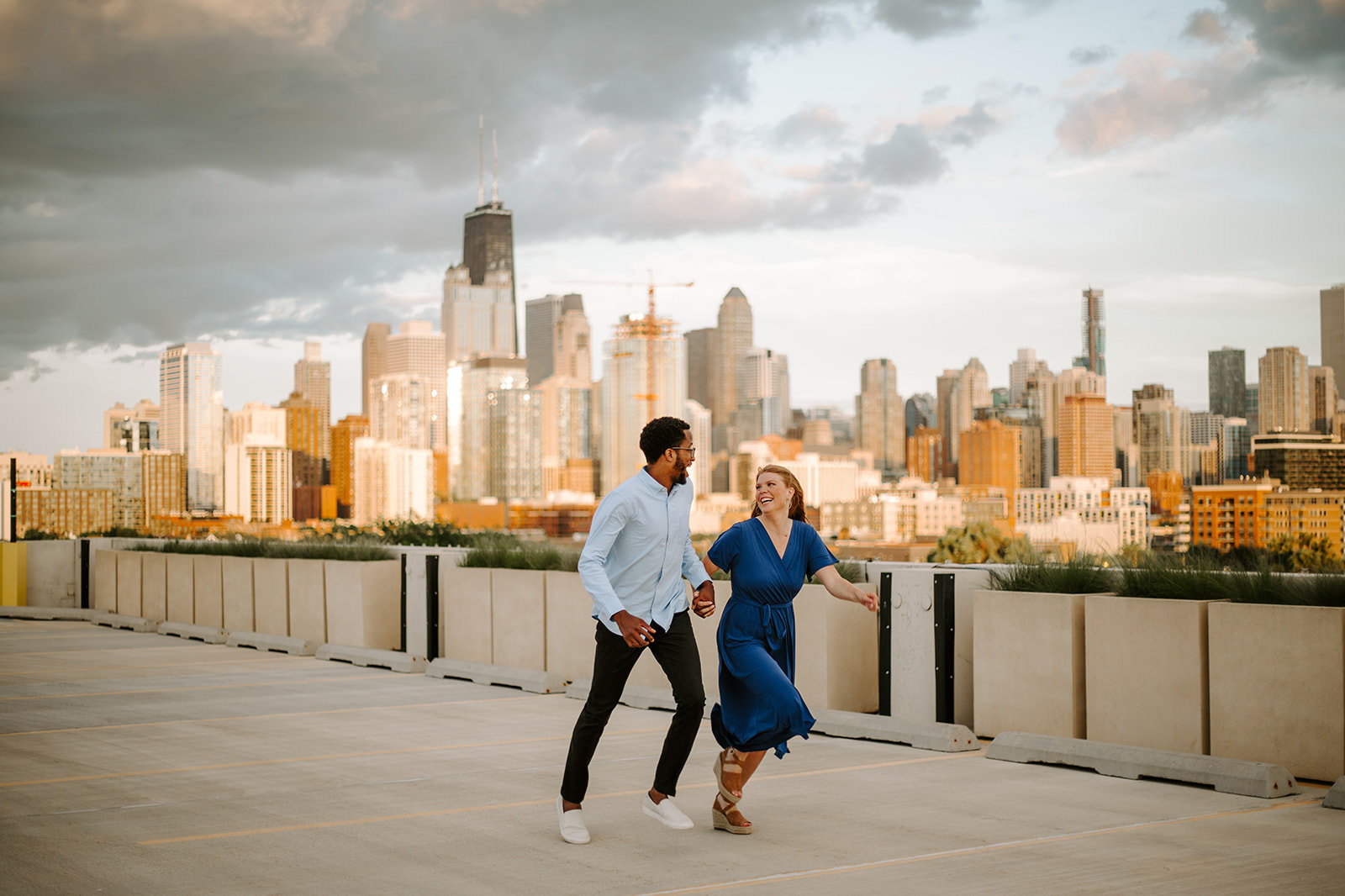 Couple holding hands running in front of the Chicago skyline during their engagement session
