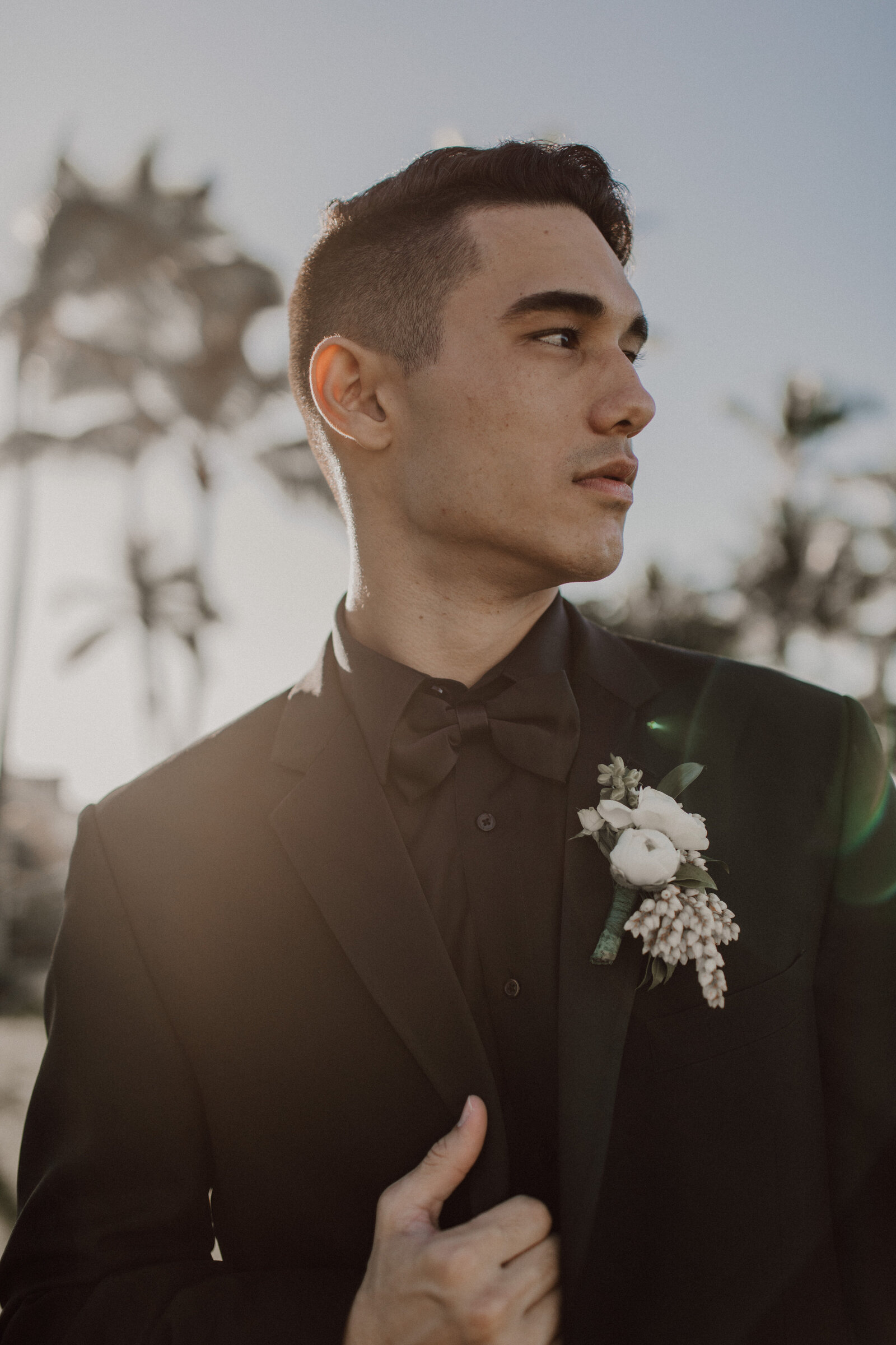 Groom-looking-into-the-distance-in-black-suit