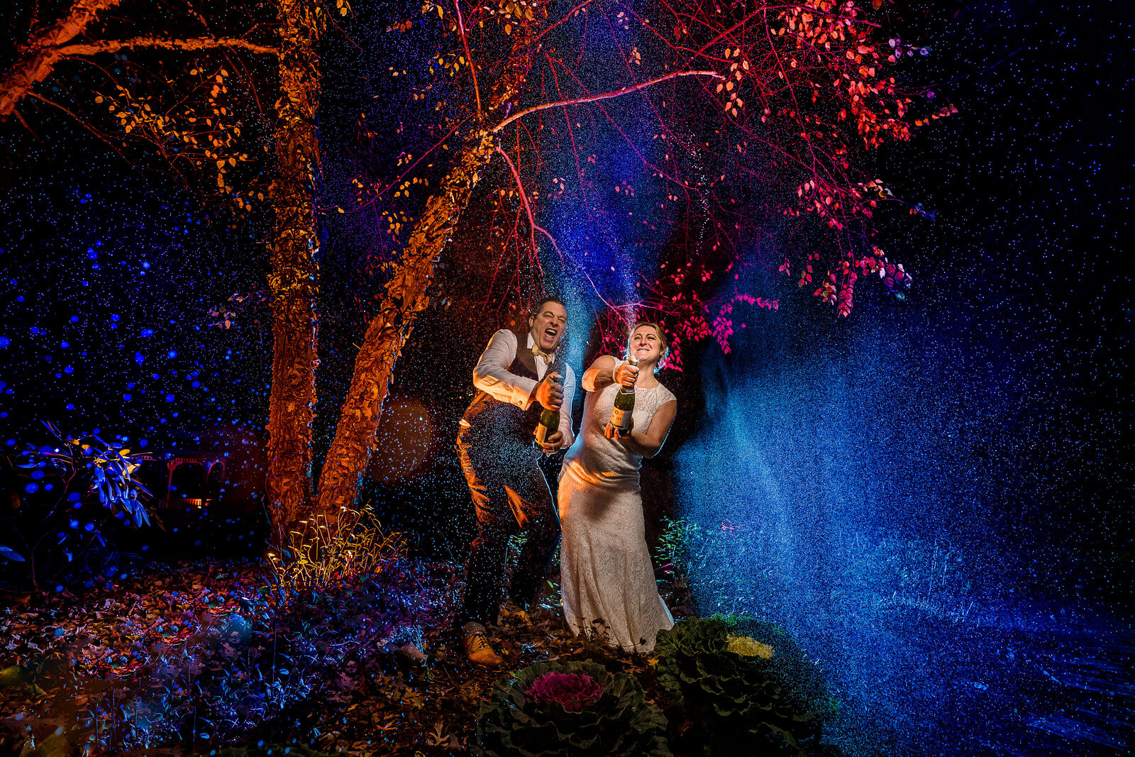 Couple sprays champagne into the air in front of a tree at old mill inn with the spray lit by colored lights