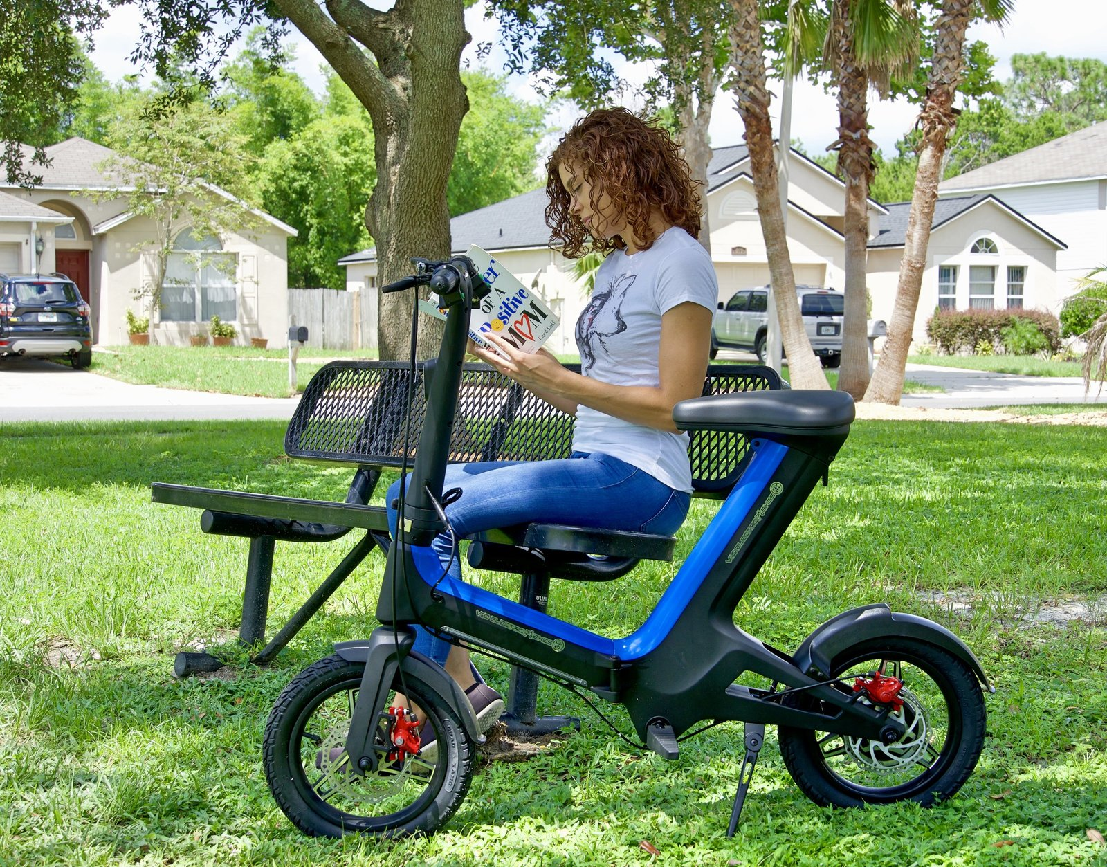 Women sitting on a bench at the park while reading a book demonstrating a Blue Go-Bike M3