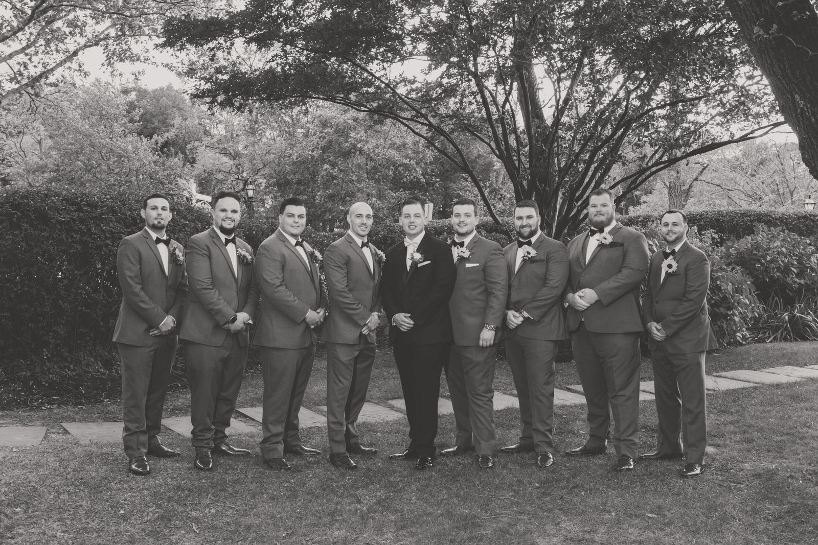 black and white photo groom with groomsmen from wedding at Three Village Inn