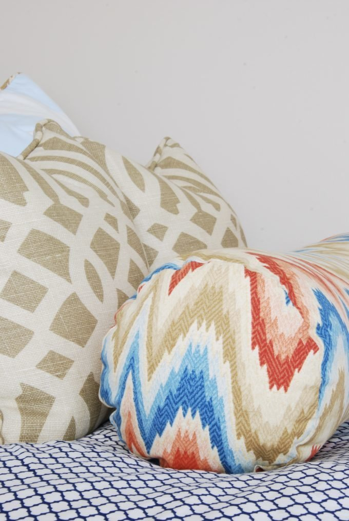 Beige, dark orange, and blue throw pillows on a bed.