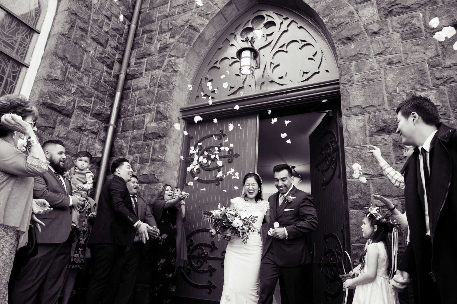 bride and groom exit church and guests throw flowers