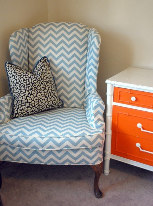 A blue and white chevron chair beside an orange and white dresser.