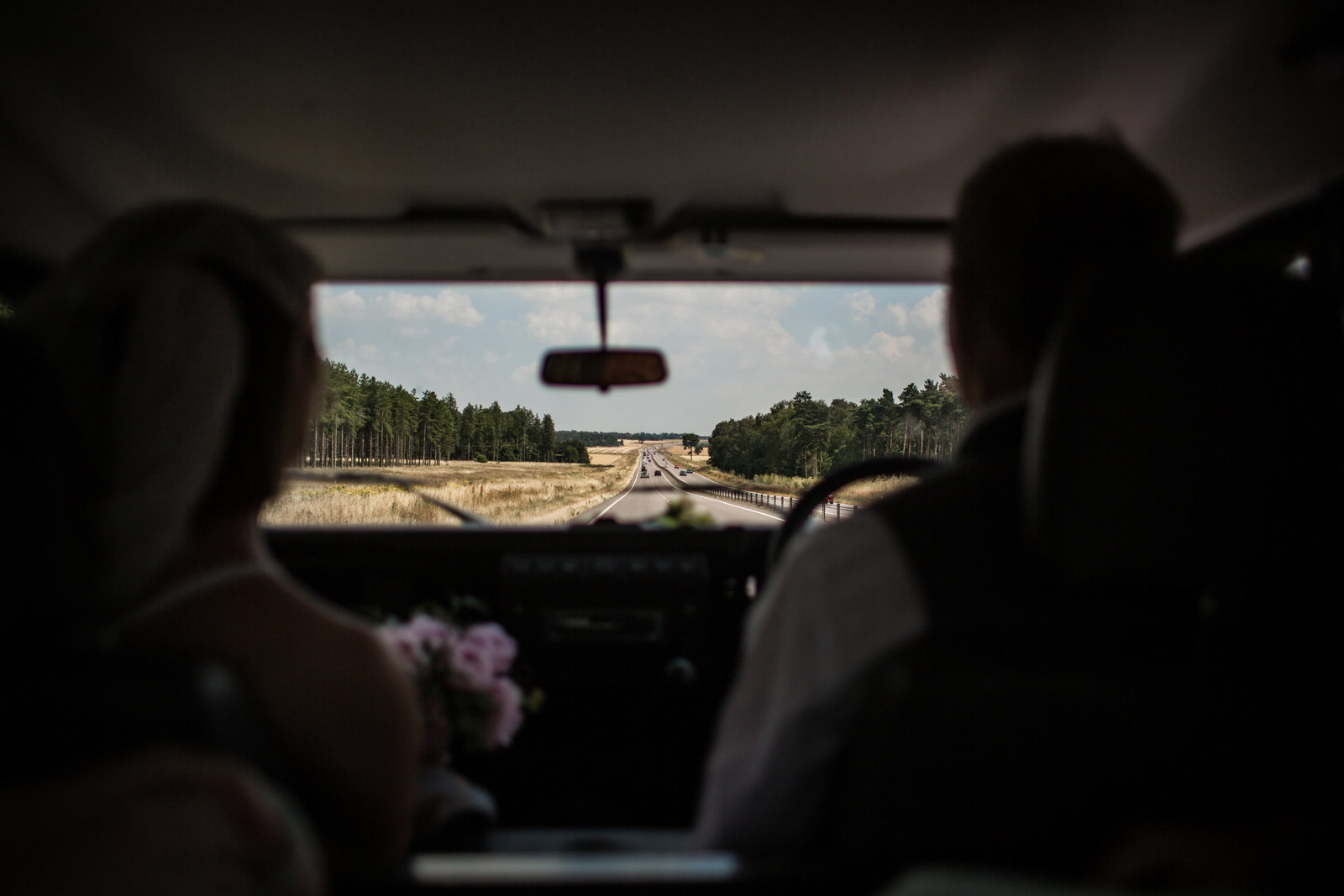 Father of the bride driving his daughter to her wedding on a summers day in Norfolk. They are in silhoutte and you can see the road ahead and dry grass.