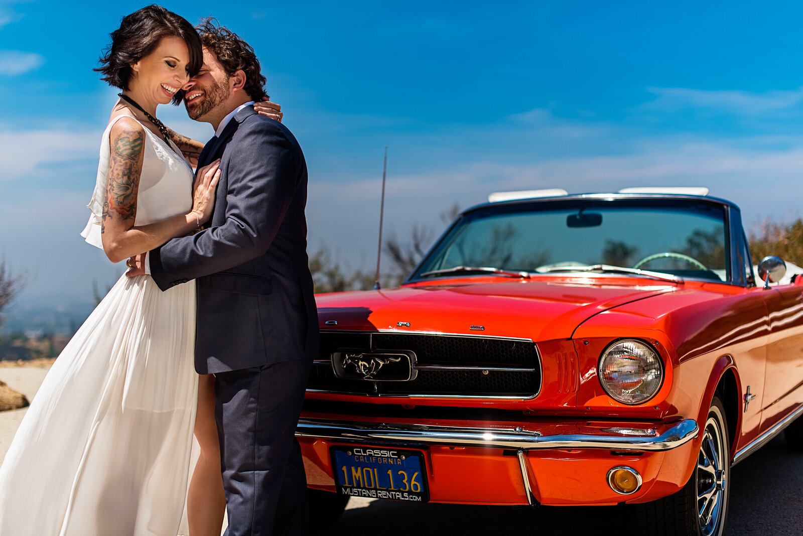 A beautiful husband a wife hired a photographer for a 10 year anniversary portrait in front of a candy apply red 1970's mustang convertible. If you're thinking about a special anniversary gift, a portrait session is an incredible idea.