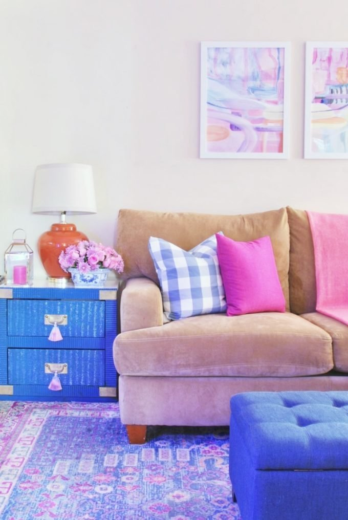A tan sofa, blue wicker end table, and blue tufted ottoman.