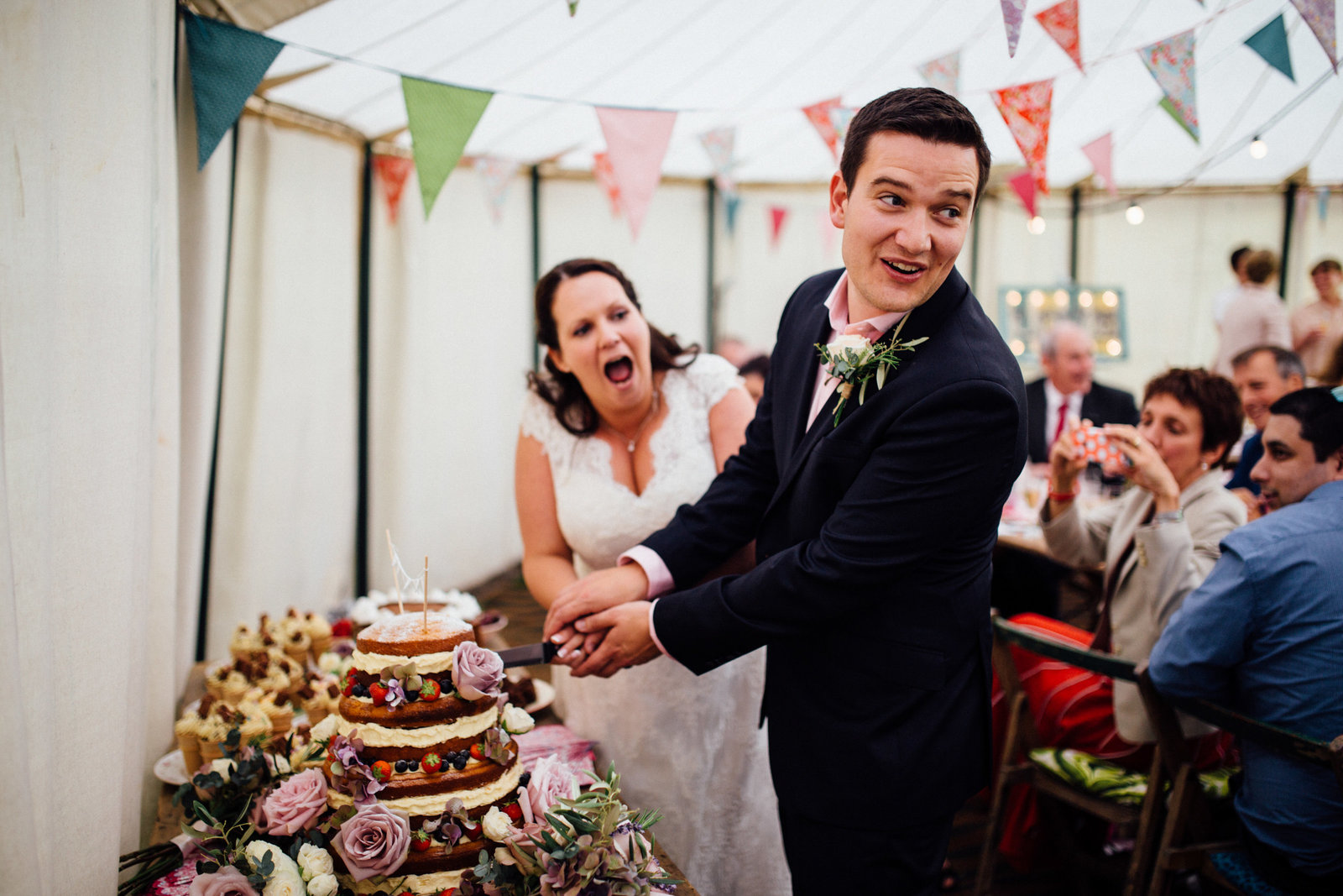 Laughing bride and groom cutting in to their naked wedding cake inside a Norfolk Suffolk marquee with bunting behind them