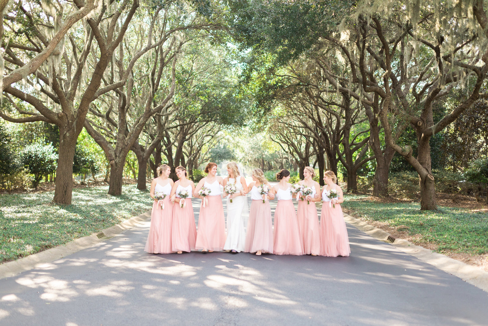 bride with bridesmaids outside under live oaks