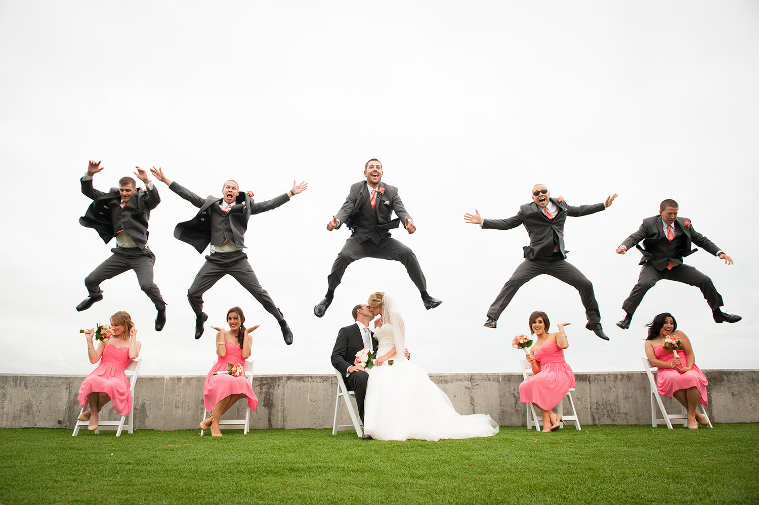 groomsmen jumping in the air at ocean view room