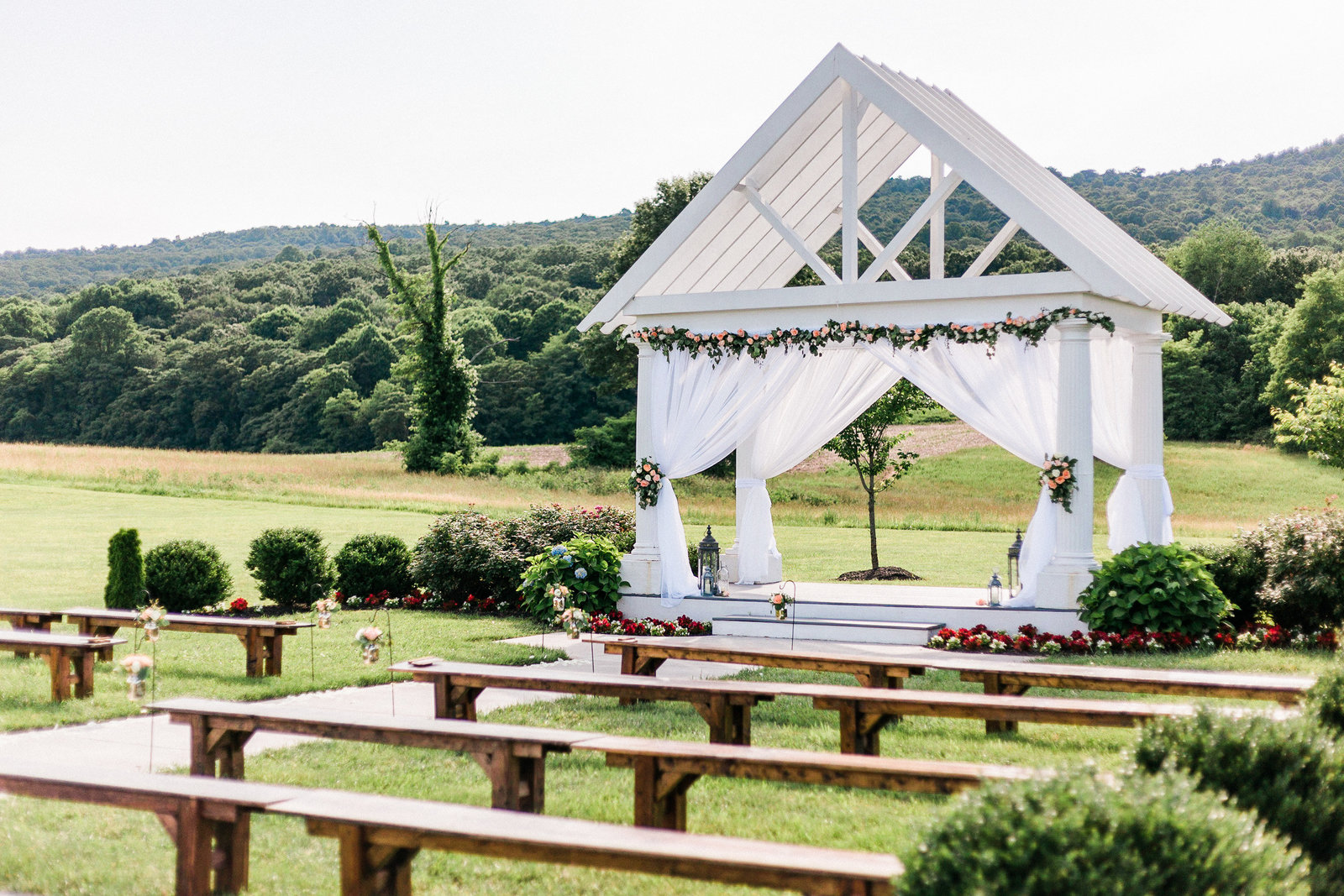 Outdoor ceremony with wooden benches and white pavilion with curtains  at Springfield Manor Maryland