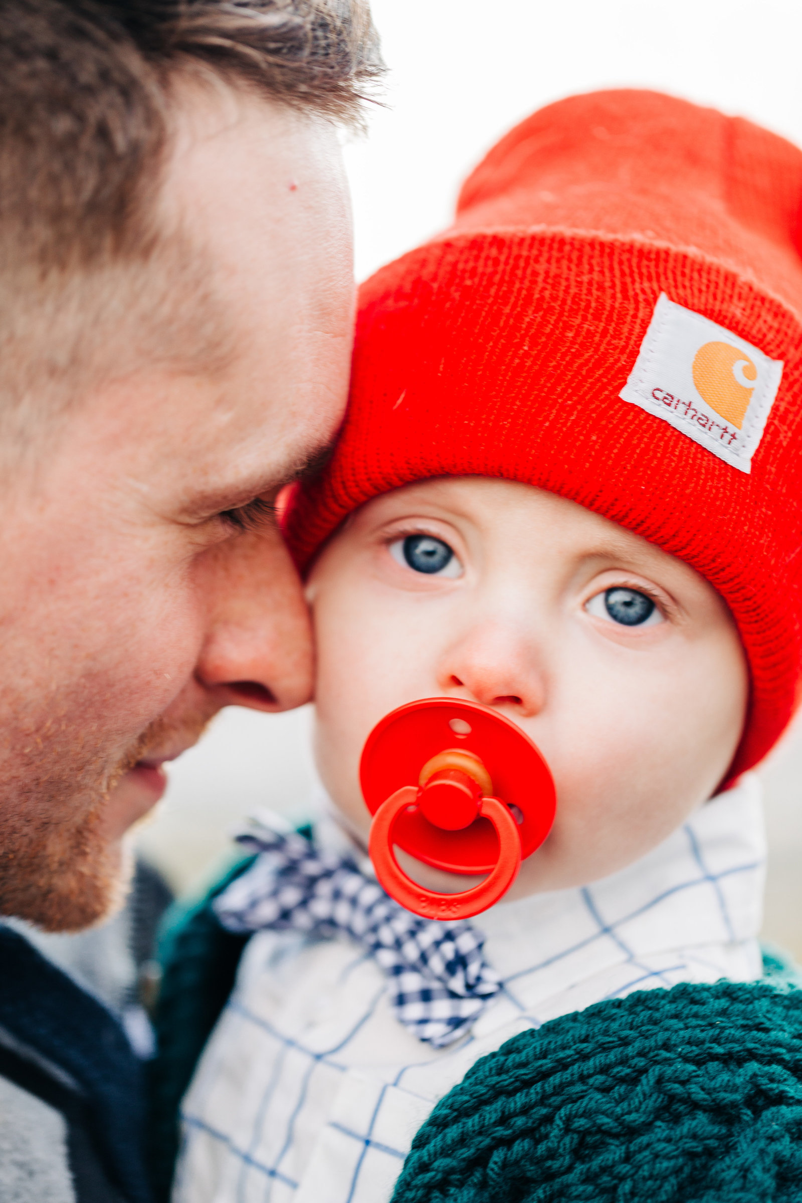 Dad snuggles his  baby who is wearing a sweater, red Carhartt hat and bowtie, sucking on a pacifier