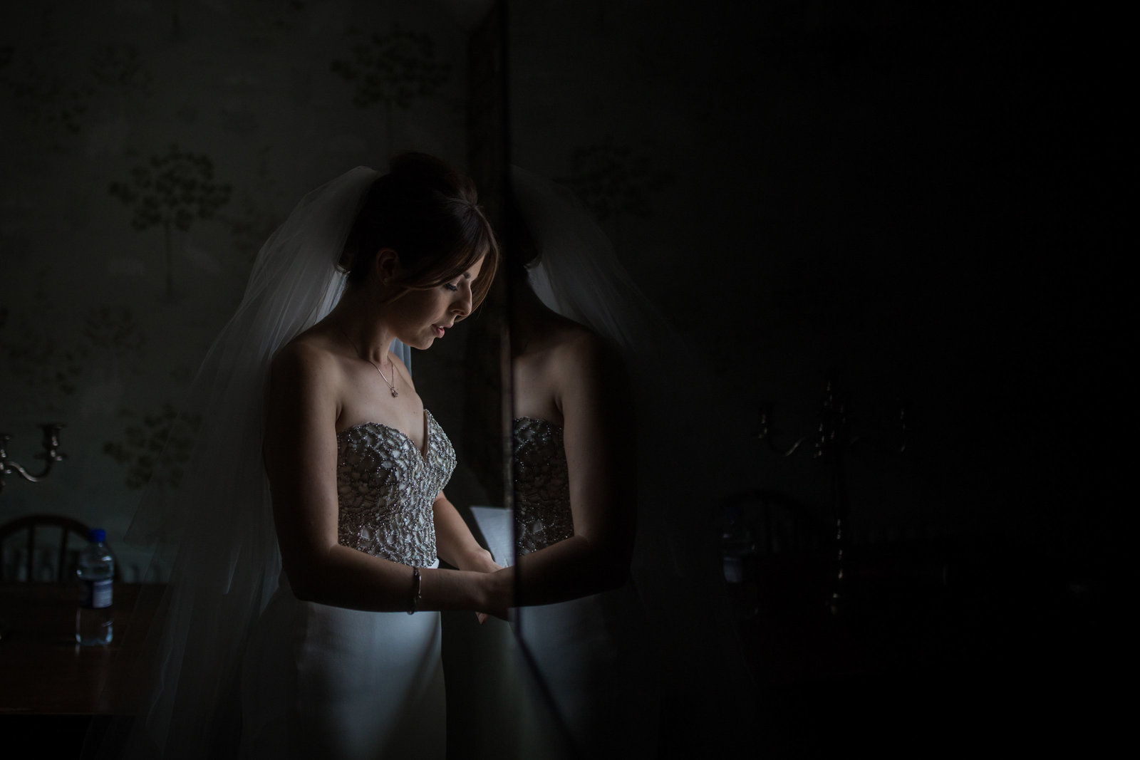 A bride stands and looks out a window on the morning of her wedding in Norwich. She is looking down and is lit by the window light.