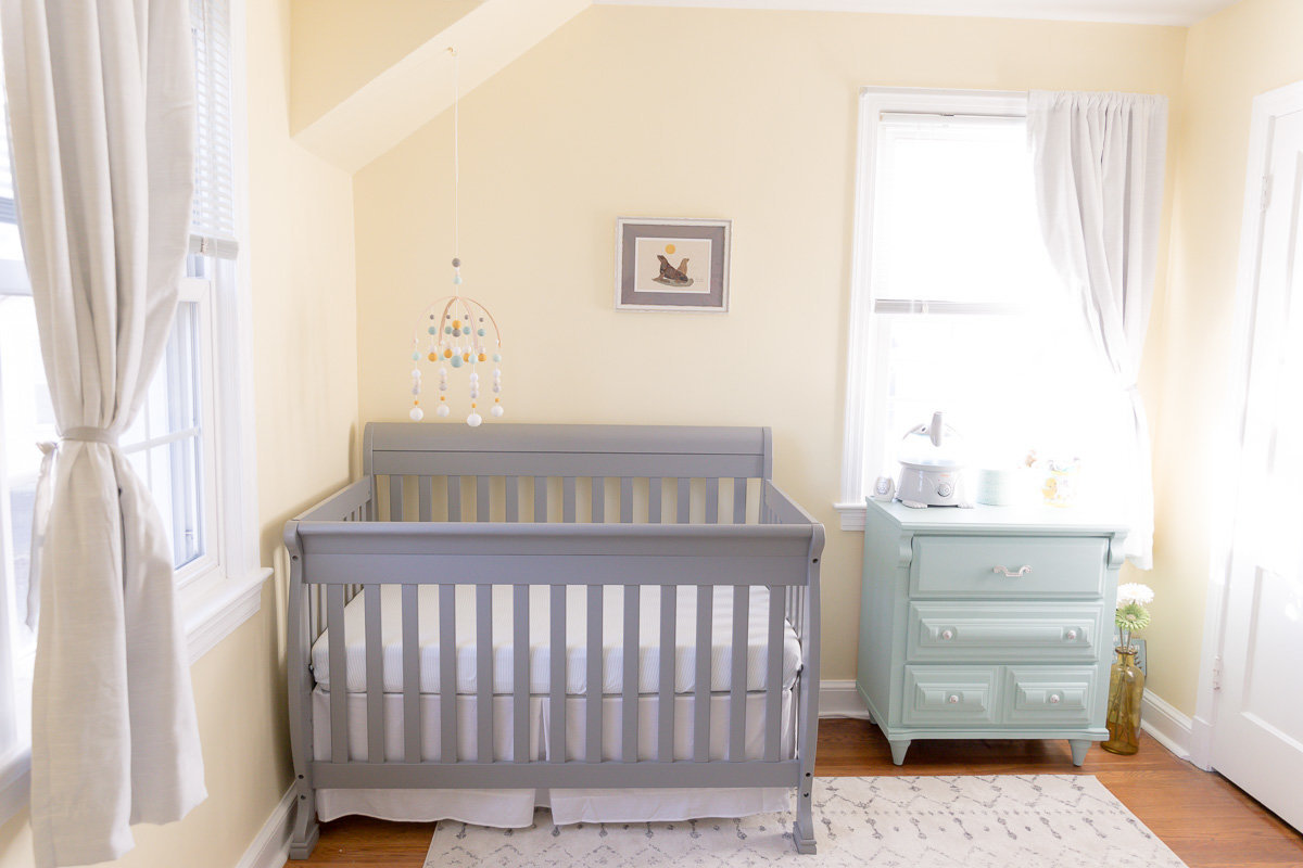 gray crib teal dresser hanging mobile in bright natural light newborn nursery