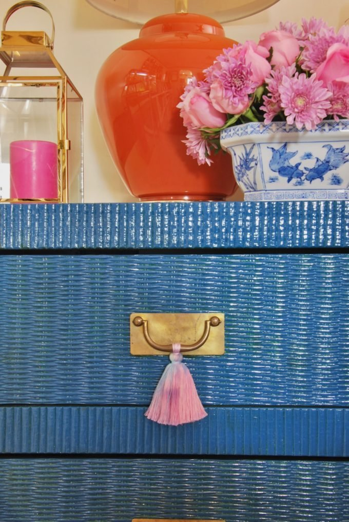 A blue wicker table with brass pull and pink tassels.