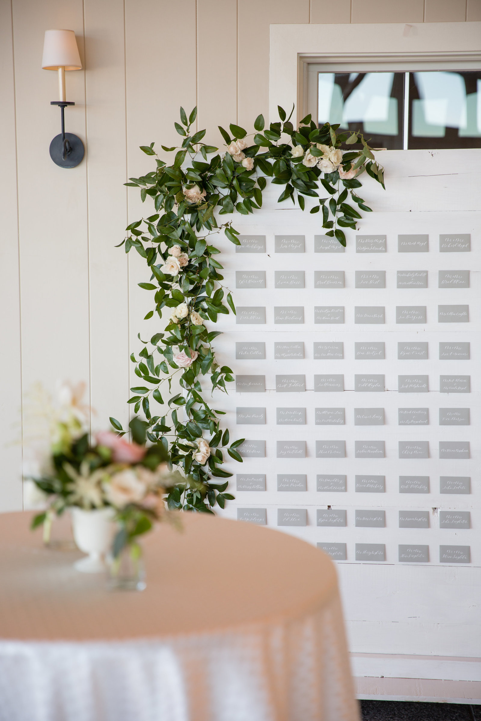 A gorgeous escort card wall and shiplap seating chart with a floral installation for Whitney Bischoff's Wedding