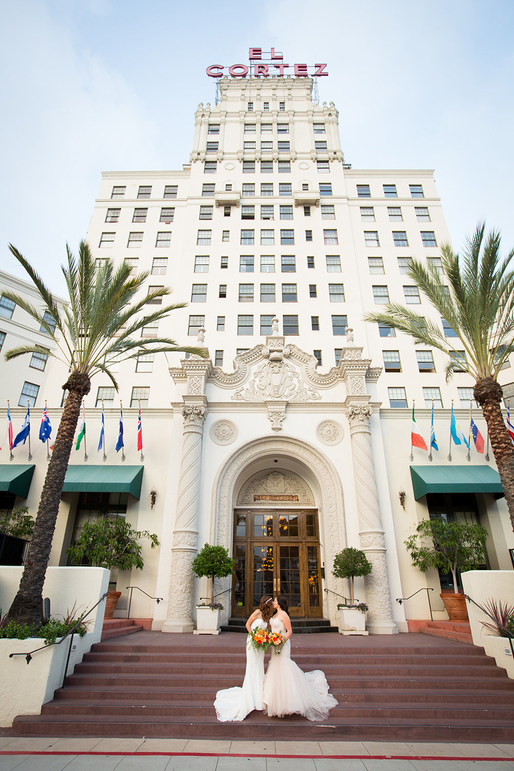 Romantic portrait of brides in front of the El Cortez in San Diego