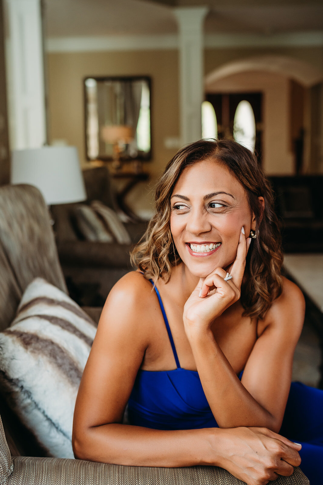 woman smiles while relaxing on a couch during brand photo session