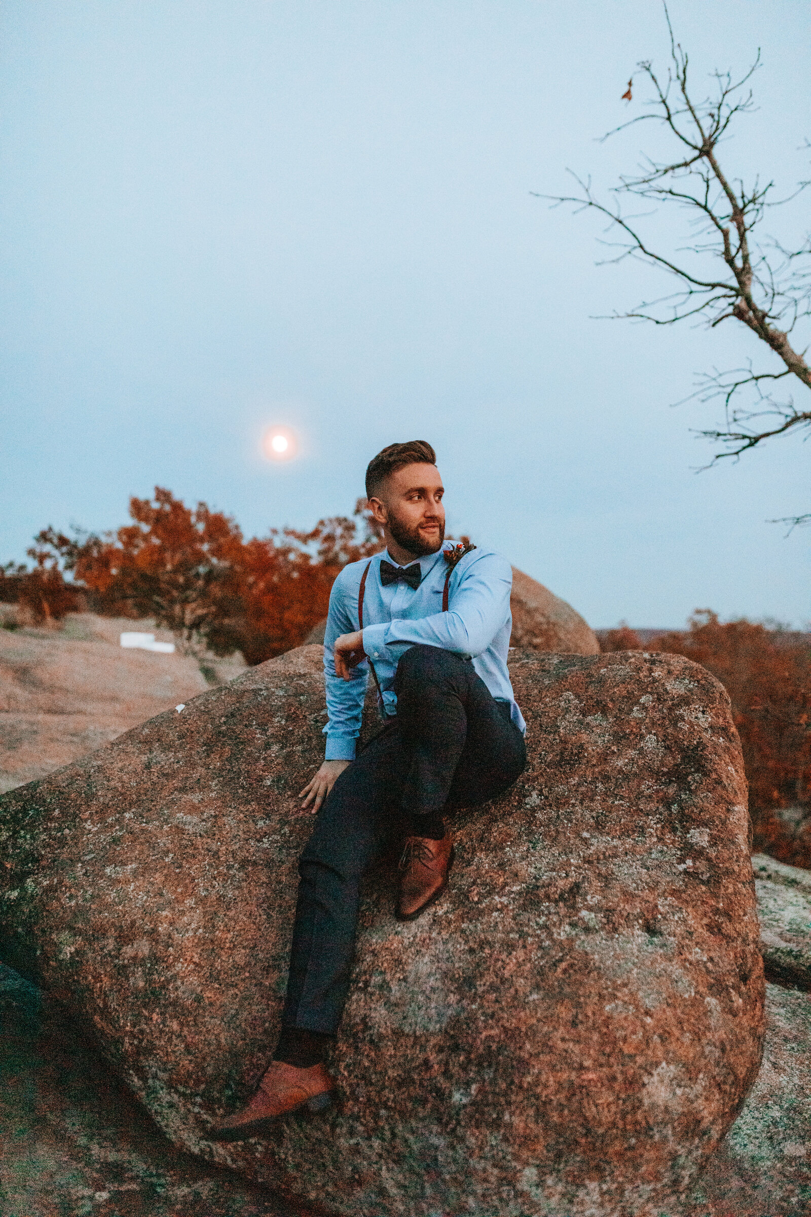husband elopement on a rock in suit and suspenders